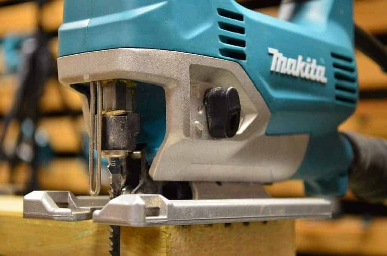A close up of Makita JV0600 jigsaw on a top of a wooden plank