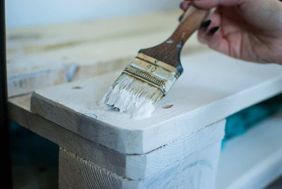 painting wooden plank white with a paintbrush