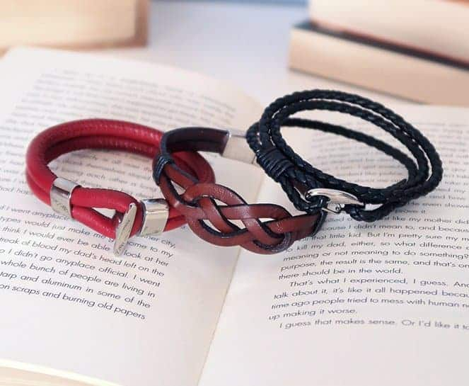 3 men leather bracelets for men on top of an open book