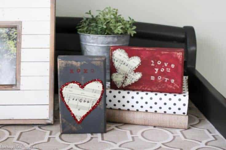 two wooden blocks with valentines decoration next to a photo frame
