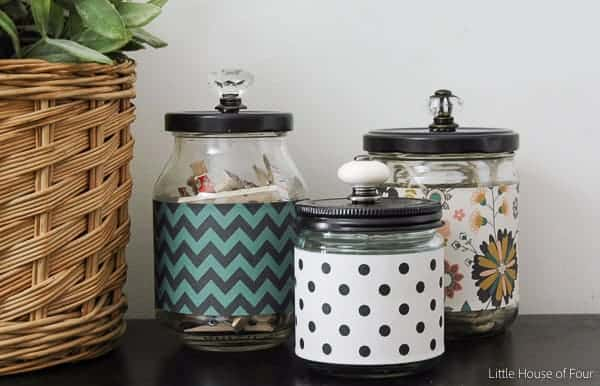 Three jars turned into storage jars next to a wicker basket plant pot