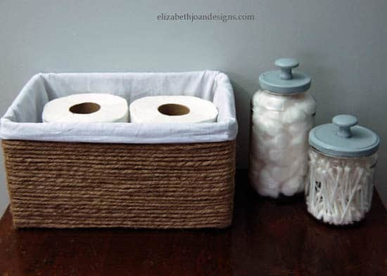 A box with 2 toilet rolls inside next to two jars, one with cotton balls and one with cotton swabs