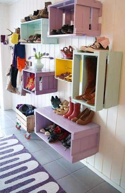 Wooden crates painted and hanging on the wall with shoes stored in them