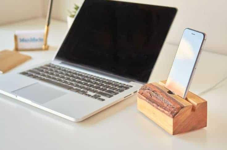 a wooden slab stand for phoe charging next to a laptop cimputer