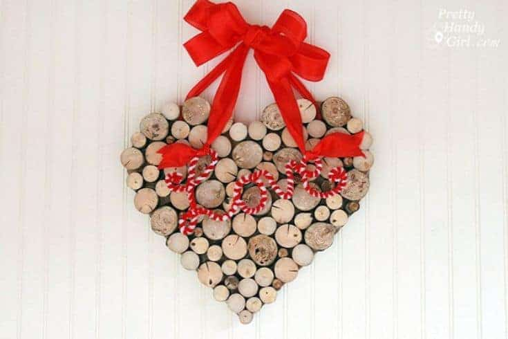 a wreath made out of cut tree branches with a red bow on top