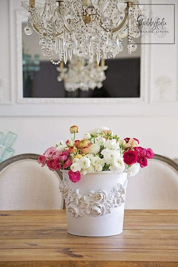 A white bucket with colorful flowers standing on the table underneath a crystal chandelier