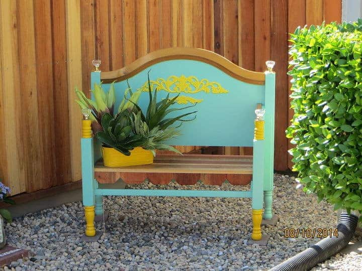 Colorful wooden bench on the grave in front of a wooden fence