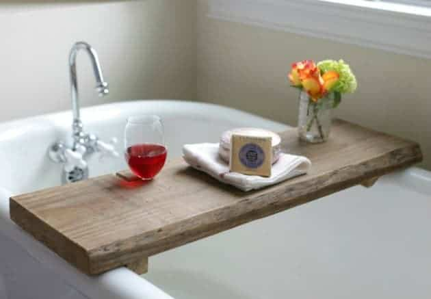 A wooden bath caddy placed on the bath with a flower pot some bath supplies and a glas of wine on top