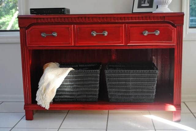 A red dresser with two black baskets and a blanket