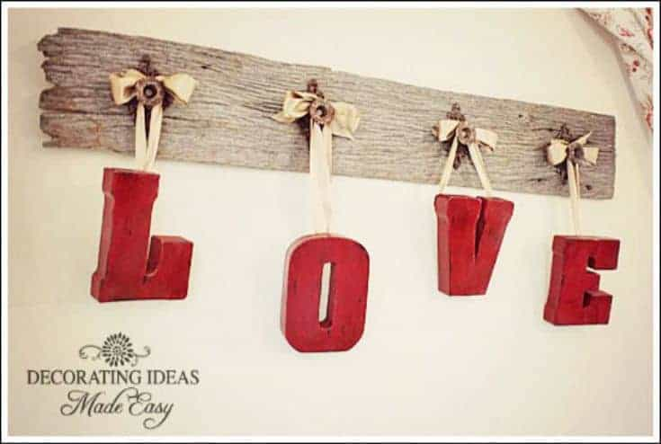wooden plank with letters hanging from knobs forming word love